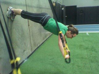 image of woman using a TRX strap to defy gravity training by Laura Coleman