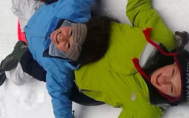 Image of two girls lying in the snow