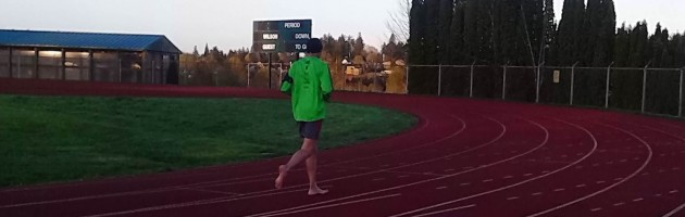 Image of a man barefoot running on a track