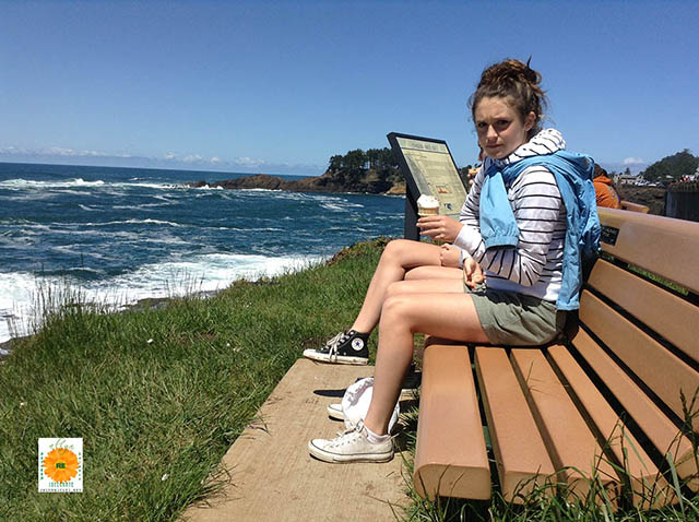 image of girl sitting on a bench at the beach
