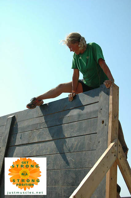 Laura Coleman at top of fence obstacle
