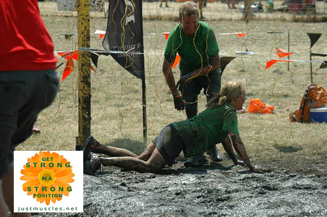 Image of Laura Coleman crawling in mud under electric shock wire