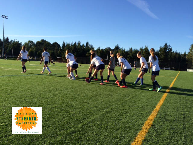 Image of a girls soccer team using dynamic stretching for warm up