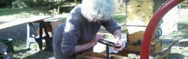 Image of an older woman using an old fashion cider press