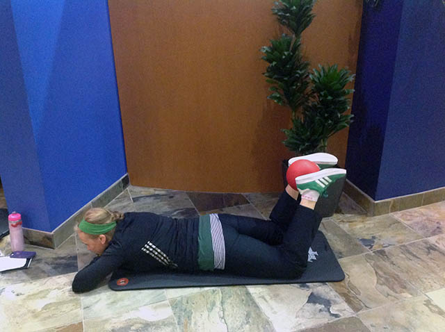 Image of Laura Coleman demonstrating prone ankle squeezes