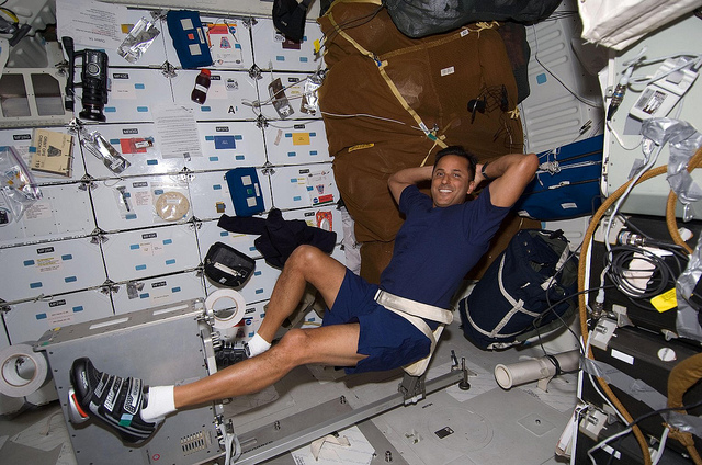 Nasa image of STS-119 Mission specialist Joseph Acaba on a shuttle exercise bike