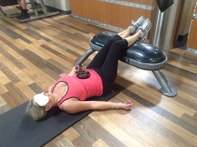 Image of woman in static back position with a weight on her stomach for breathing control
