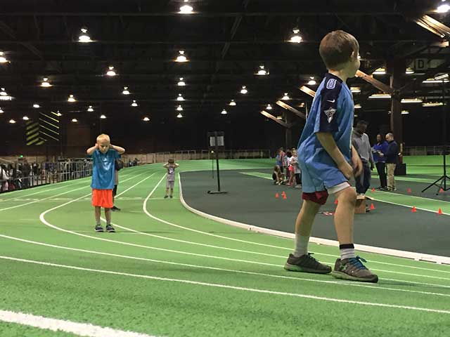image of small boys on an indoor running track