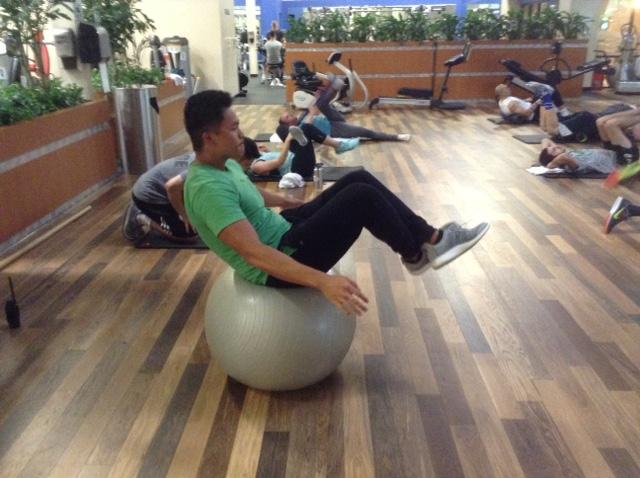 Image of man balancing on balance ball without using hand or feet