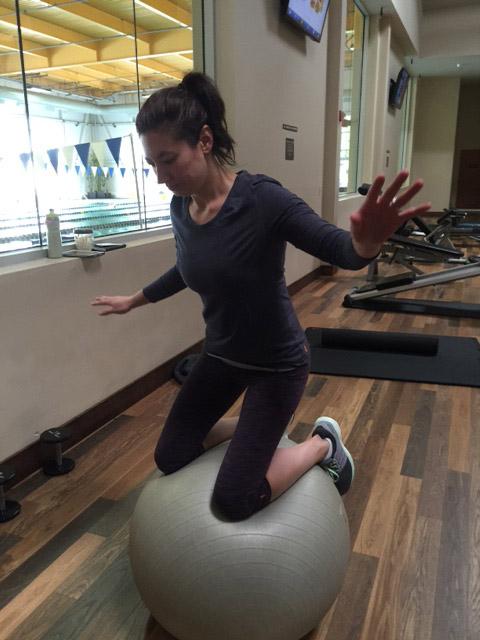Image of woman knee balancing on balance ball