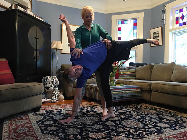 Image of personal trainer, Laura Coleman doing a partner half moon hip opener stretch