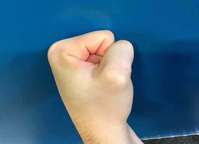 Image of hands in a thumb fist hands yoga strengthening position