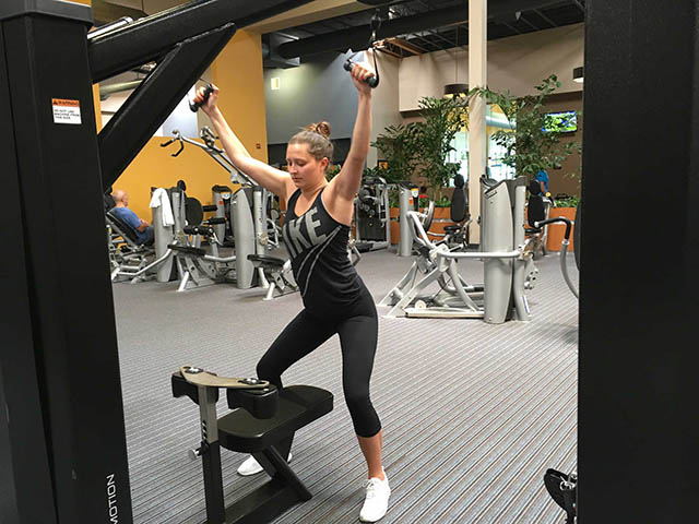 Image of woman using cable machine for lat pull down