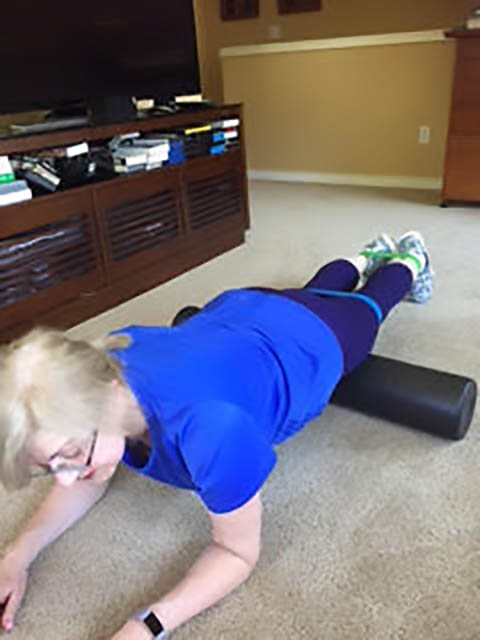 Image of a woman lying face down with her quads on a roller