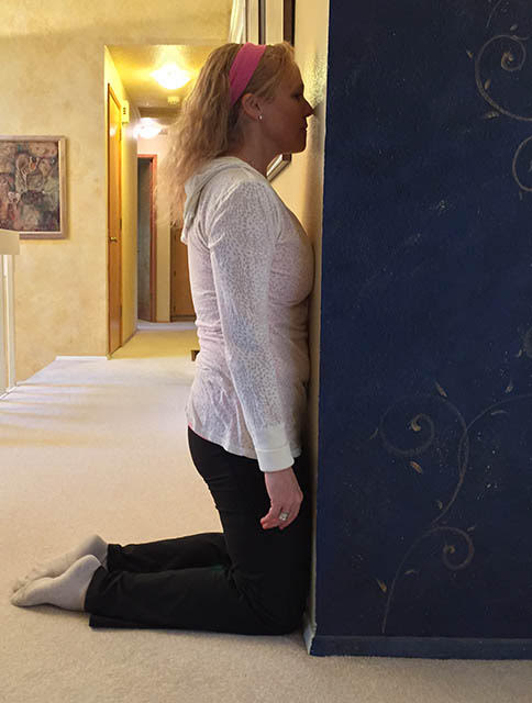 Image of trainer, Laura Coleman, demonstrating kneeling wall exercise