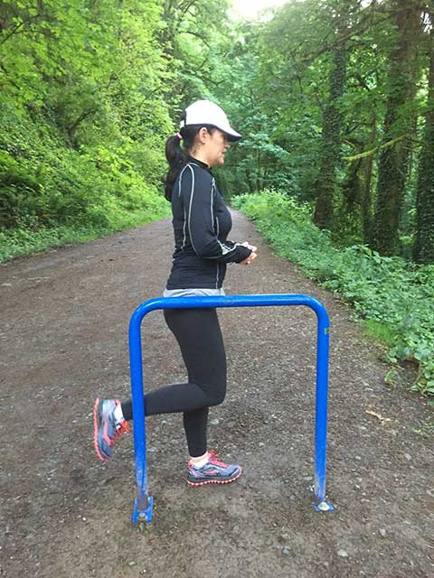 image of a woman doing warm up hamstring curls on a trail