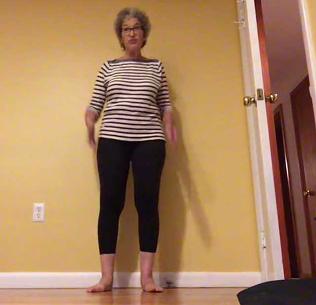 Image of someone standing against wall to help find her glute muscle