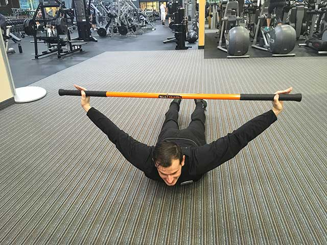 Image of man demonstrating cobra stretch exercise using a moving stick in a gym