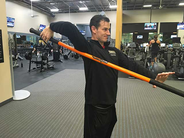 Image of man showing a shoulder movement exercise with moving stick