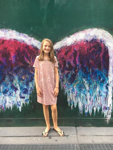 Image of young girl in front of angel wing graffiti art